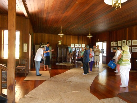 Tour guide at Vailima speaking in the great room. Notice the beautiful natural grass mats on the floors.