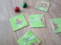 Several Caracassonne tiles and 2 of the follower pieces