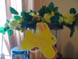 A bunny wreath draped over a hurricane candle