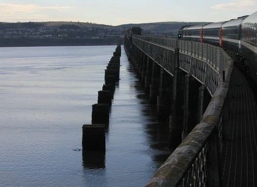 The new Tay bridge with a train travelling along. Beside this you can see the stumps of the old bridge that collapsed killing 75 people.