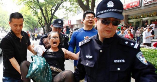 Chinese police arresting Tibetan woman