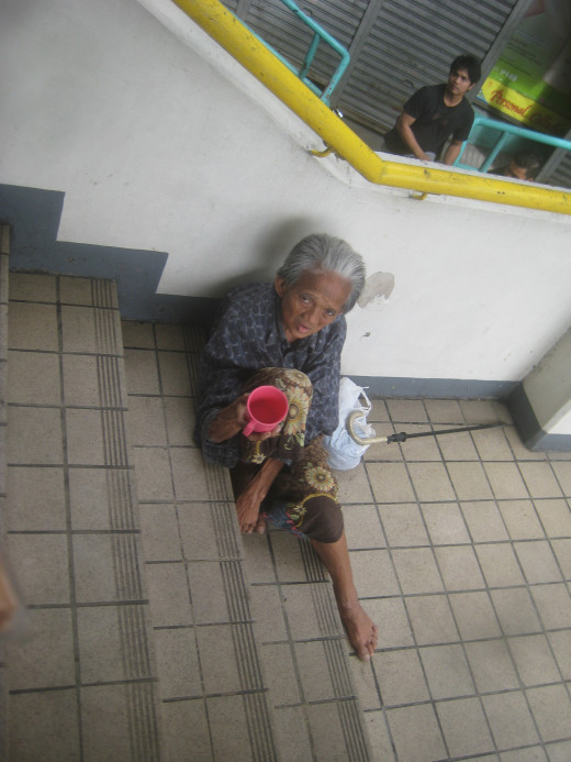 A beggar - an old woman in the Philippines asking for alms stationed at the stairs of LRT station (Photo Source: Ireno Alcala aka travelman1971)