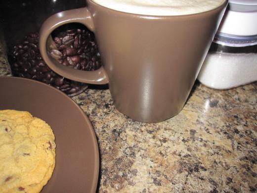 Cafe latte alongside granulated sugar