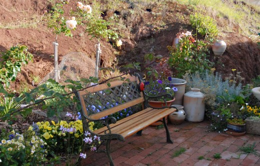 A garden bench surrounded by pottery