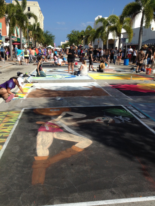 The artists line the street to transform the pavement into works of art.