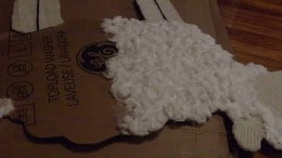 Continue gluing down cotton balls in small sections until lamb is covered in them.