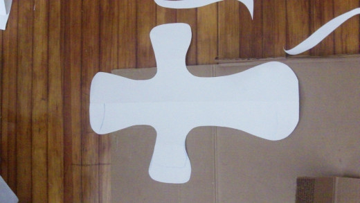 Fold paper in half and cut out a cross shape.