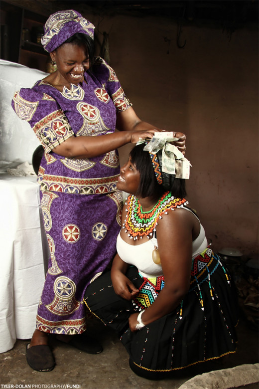 A Zulu teen receives motherly blessing during her Umhlonyana ceremony. Image by Tyler Dolan.