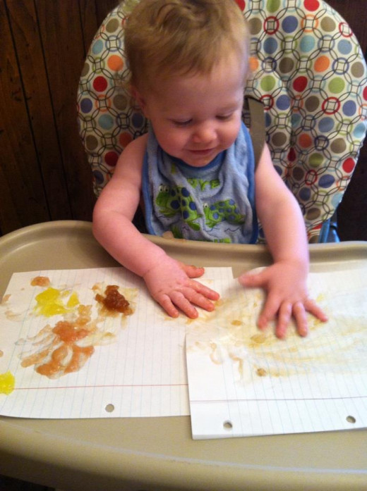 An unschooled child exploring and learning with edible finger paint.