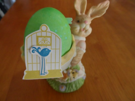 Stamped and cut out punch art designs, bird and bird cage in egg holder.