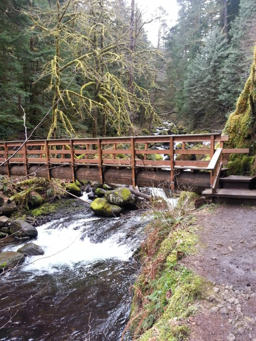 A large wooden bridge crossing the river above the fall.