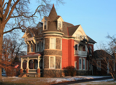 A Victorian with a castle-like tower and exterior stone accents.