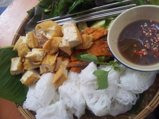 Bún đâu mắm tôm consists of fresh leaf rice vermicelli, fried tofu, shrimp paste dipping sauce and table salad (fragrant herbs)