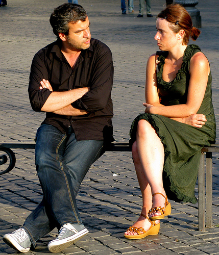 Notice how not only are their arms crossed, but their legs too... the precursor to the wrath of a jealous girlfriend.