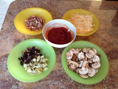 Pizza ingredients - sliced Crimini mushrooms, marinated artichokes, olives, apple smoked bacon, tomato paste, shredded cheese (Mozzarella, Monterey Jack, Cheddar, Parmesan)