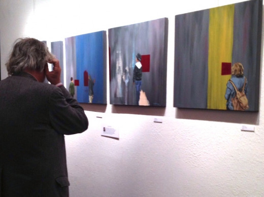 A man contemplating paintings. Photo and paintings by Corinna Nicole.