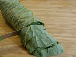 Roll collard green leaves into a cylinder shape, then cut 3/4 inch slices.
