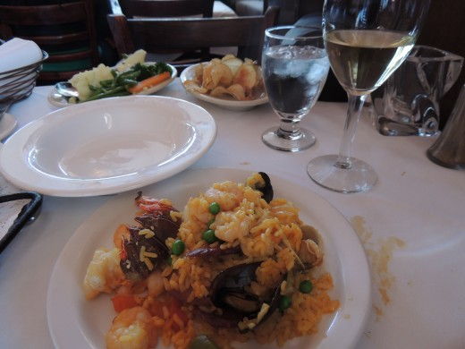 Mixed vegetables and homemade potato chips are served along with the paella and wine.