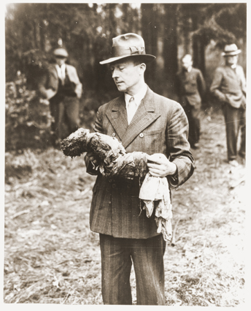 A German man holding a baby from a mass grave.