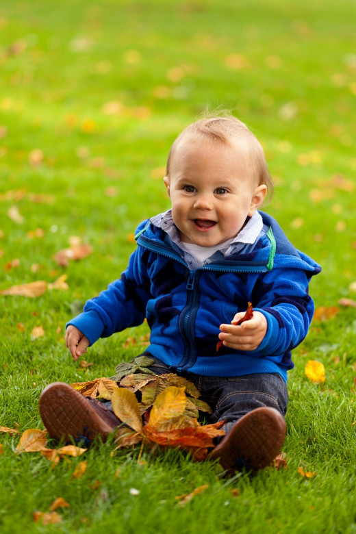 A cheerful child, enjoying the novelty of his first autumn!