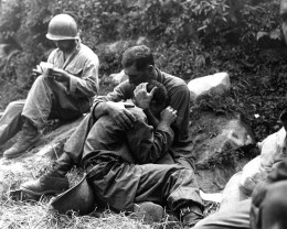 Msgt Frank Chandler, US Army 5th Regimental Combat Team, comforts a soldier who had just identified his best friend's body.