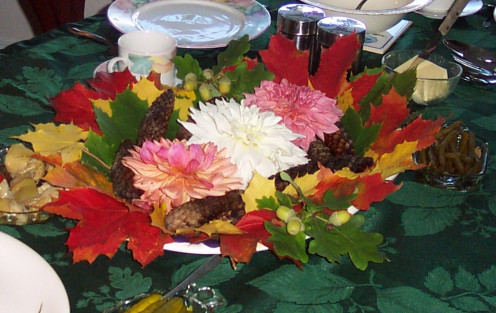 Huge late flowers are surrounded by brightly-colored leaves, pine cones, and assorted nuts.