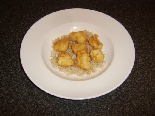 Battered chicken is laid on bed of fried rice