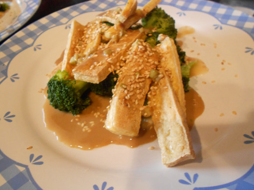 Plated broccoli with tofu and peanut sauce, topped with sprinkled toasted sesame seeds