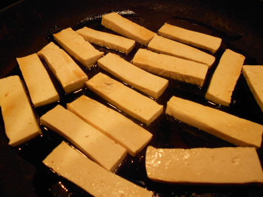 Cut the Tofu into slices and place in a skillet. Coat with sesame or oilive oil before cooking.