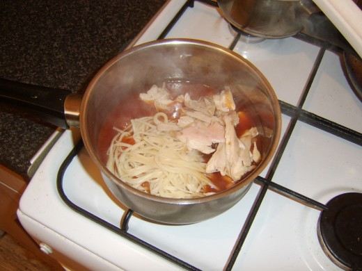 Chicken and noodles are added to sweet and sour sauce