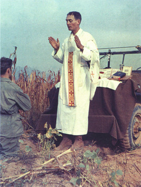 Father Kapaun conducts services with the hood of his Jeep serving as an altar