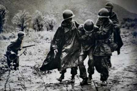 Father Emil Kapaun (right) and a doctor carry an exhausted Soldier off a battlefield in Korea, early in the war. The photo shows Kapaun to the GI's left. The soldier on the GI's right side was Capt. Jerome A. Dolan, a medical officer with the 8th Cav