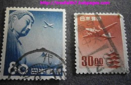 Two Japanese airmail stamps from the 1950s. The stamp on the left features a plane flying over the Great Buddha of Kamakura.