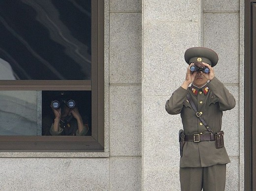 North Korean soldiers looking south while on duty at the border.