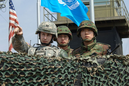 An American Army captain observes the north alongside two South Korean soldiers.