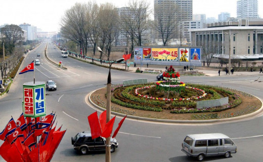 "A ""busy"" traffic circle in Pyongyang decorated for Kim Il Sung's 99th birthday, April 2011. The billboard is for propaganda."