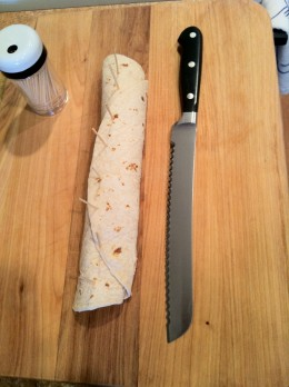 One complete tortilla roll ready for slicing into individual pieces using a serrated knife.