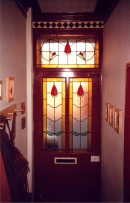 Stained glass in front door lights up the hallway.