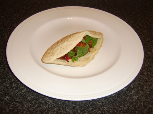 Chicken and vegetables are grilled on a skewer, stuffed in to a pitta bread and drizzled with sweet and sour sauce