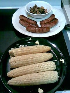 Fresh buttered corn on the cob and sausage with mushrooms and onions fresh off the grill