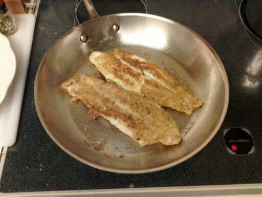 Frying the second side of the two fish fillets.