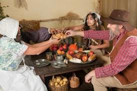 Some re-enactors showing Indians and Pilgrims eating together