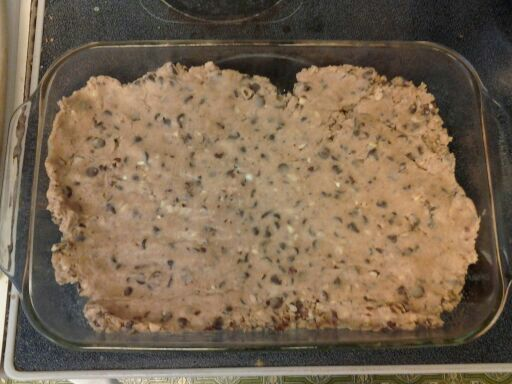 Spreading the cookie dough into the baking dish