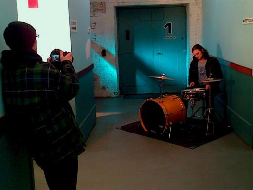Director/photographer Jeff Rich (left) shoots footage of drummer Alex Petropulos in a hallway outside of Best Not Broken's rehearsal room.