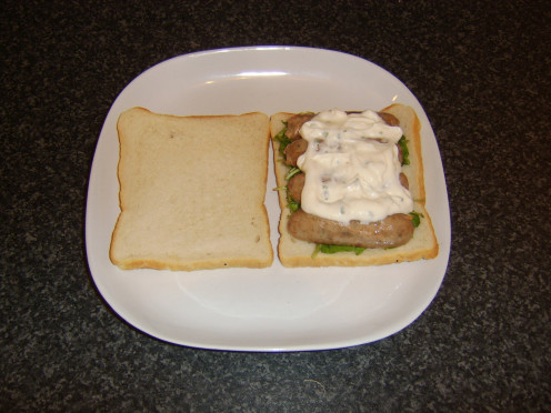 Cold pork and herb sausages on a watercress bed, topped by garlic and chive mayo sandwich
