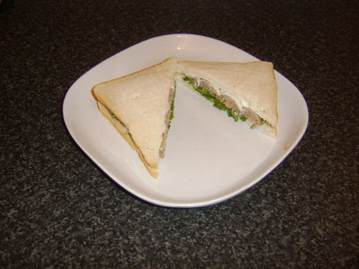 Sausage watercress and mayo sandwich is sliced to serve