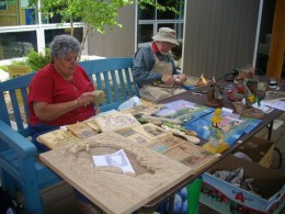 First Nation and Mennonite representatives at a booth at Visitor Centre carving products out of wood.