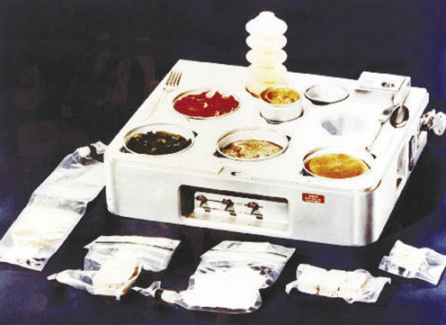Very old Skylab food heating and serving tray with food, drink, and utensils. NASA aand private researchers still have work to do in food service and nutrition in space.