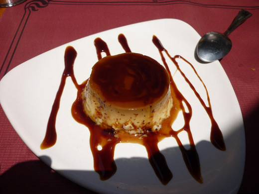 Coffee Flan plated with decorative caramel syrup.