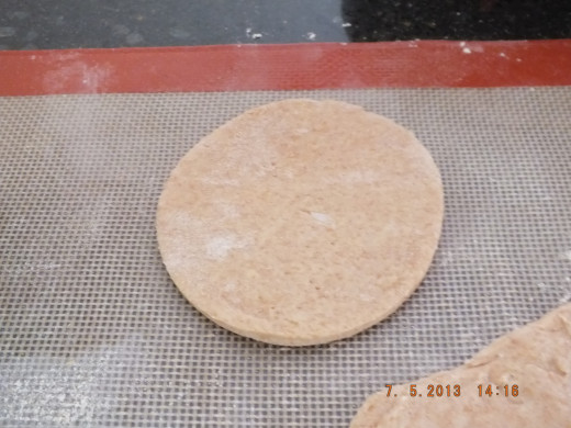 Take your circle and put about a tablespoon of filling on one half of the circle along with a line of water all around the outer circle edge. This will act as glue and hold the pierogi together. Then take the other side and stretch it out.
